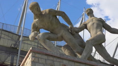 Athlete statue and PGE Narodowy, National Stadium, Warsaw - summer - pan Stock Footage