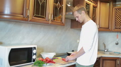 Smiling man preparing salad in the kitchen Stock Footage