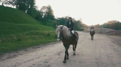 Couple of proffesional jockeys man and woman are riding horses at the Stock Footage