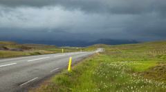 High contrast sun and storm clouds mountain road traffic Iceland 4k Stock Footage