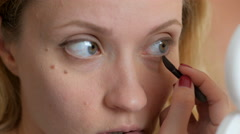 Big green eyes of young woman doing makeup by brown shadows close-up Stock Footage