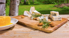 Rustic table with honey, cheese and nuts on the background of birch trees Stock Footage