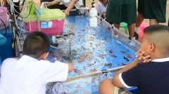 Thai children playing goldfish scooping game Stock Footage