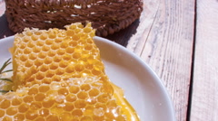 Panorama of honey cells in a white plate on a wooden table Stock Footage