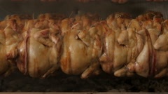 Chickens turning and roasting on electric spit, close up by Sheyno. Stock Footage