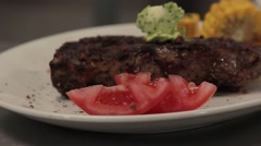 Fried rib eye steak on a plate, close up, sliding Stock Footage
