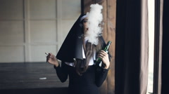 Bad nun drinks alcohol and smokes Stock Footage