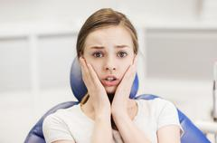 scared and terrified patient girl at dental clinic - stock photo
