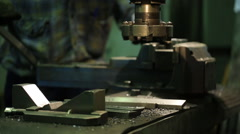 Factory worker sets metal piece in vise of a milling machine Stock Footage