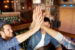 close up of friends making high five at bar or pub - stock photo