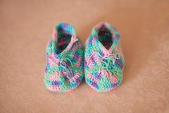 Knitted baby booties on a sofa, hand made - stock photo
