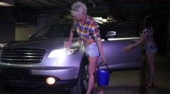 Two women wash the door and the headlamp of the car in the parking Stock Footage