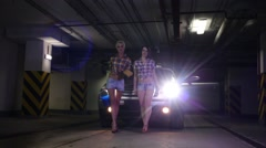 Two women walk towards the camera from the car and squeeze sponges Stock Footage