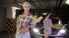 Two women standing in the parking lot next to the car Stock Footage