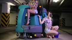 Woman drives scrubber machine next to it is the second woman Stock Footage
