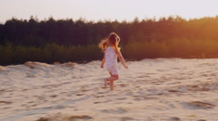 Carefree girl 3 years running through the sand toward the setting sun. Against Stock Footage