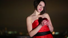 Beautiful brunette in a red dress with an apple outdoors Stock Footage