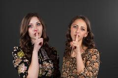 Two girlfriends are asked to be silent, do not tell anyone Stock Photos