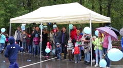 Many children and adults with balloons standing under a canopy Stock Footage