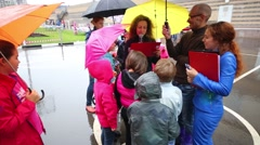 Children stand around a woman with a microphone under umbrellas Stock Footage