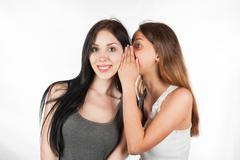 Two happy young girlfriends whisper talking, society gossip, rumor, rumour Stock Photos