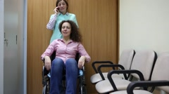 Nurse and patient in a wheelchair, the nurse talking on the phone Stock Footage
