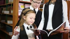 Three children - a boy and two girls read the book in the library Stock Footage