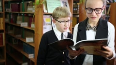 Girl and boy stands in the library and read a book together Stock Footage