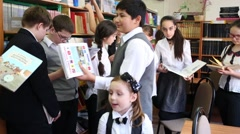 Eleven schoolchildren are taking the book from the shelves in the library Stock Footage