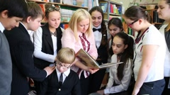Twelve people - the teacher reads to schoolchildren in a library book Stock Footage