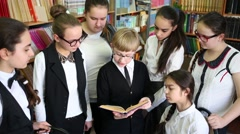 Seven schoolchildren in library - girl around a boy who is reading book Stock Footage