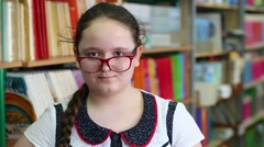 Girl corrects glasses with a finger next to a bookshelf in library Stock Footage