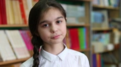 Girl with pigtail and a white blouse in the library at the book shelves Stock Footage