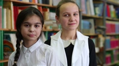 Two girls standing at the bookshelves in the library Stock Footage