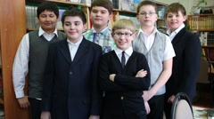 Six boys standing at the bookshelves in the library and leave Stock Footage