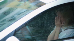 sad girl crying in the car. rain on the street. woman in hysterics - stock footage