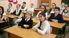 Thirteen children sitting in a classroom at school desks and raise hands Arkistovideo