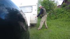 Man checks white  caravan ,trailer . Life on travel Stock Footage