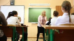 Seven people in the class: teacher going and talking with students Stock Footage