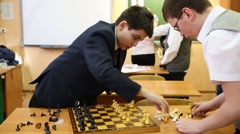 Two boys put the chess pieces, teacher and other children in the background Stock Footage