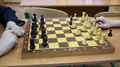 Hands of two boys playing chess on the desk in the classroom Stock Footage