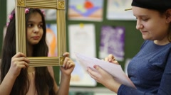 Two girls in the classroom, one paints a portrait of another Stock Footage