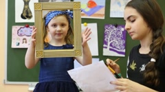 Two girls in the classroom painted portrait from life Stock Footage