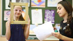Two girls in the classroom, one of them posing for a portrait Stock Footage