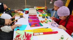 Children paint sitting at a table in the courtyard at feast of knowledge Stock Footage