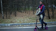 A man with a small child near the forest on the scooter on the road Stock Footage
