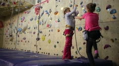 Two girls pulling a safety rope next to the climbing wall Stock Footage