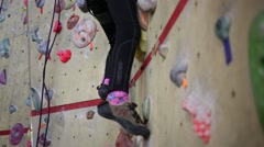 Girl climbs the climbing wall in the climbing shoes and body harness Stock Footage