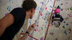 Girl climbing on the wall, a man hedging is not in focus Stock Footage