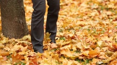 Man kicks the dry leaves near the tree in autumn park Stock Footage